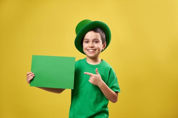Menino feliz com roupas verdes e chapéu irlandês coloca o dedo indicador em uma folha de papel com espaço de cópia e sorri enquanto posa em uma superfície amarela