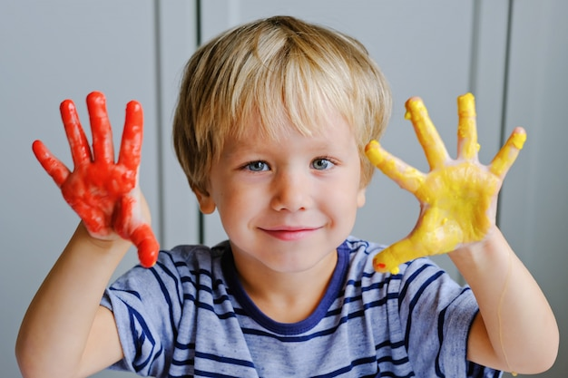 Menino feliz com três anos de idade, pinturas de dedo de pintura