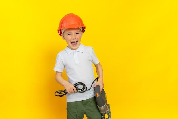 Menino feliz com um quebra-cabeça de ferramenta elétrica em uma parede amarela, vestido com um capacete e uma camiseta branca conceito de desenvolvimento infantil futura profissão na indústria da construção