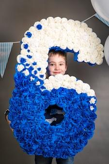Menino feliz comemorando aniversário com um grande número seis de flores