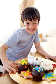 Menino feliz comendo confeitaria colorida