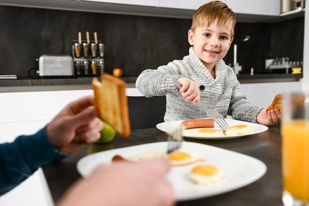 Menino feliz comendo na cozinha com seu pai. concentre-se no menino.