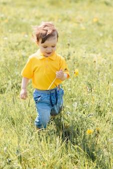 Menino feliz corre e brinca ao ar livre em um campo