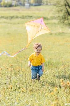 Menino feliz correndo ao ar livre com uma pipa