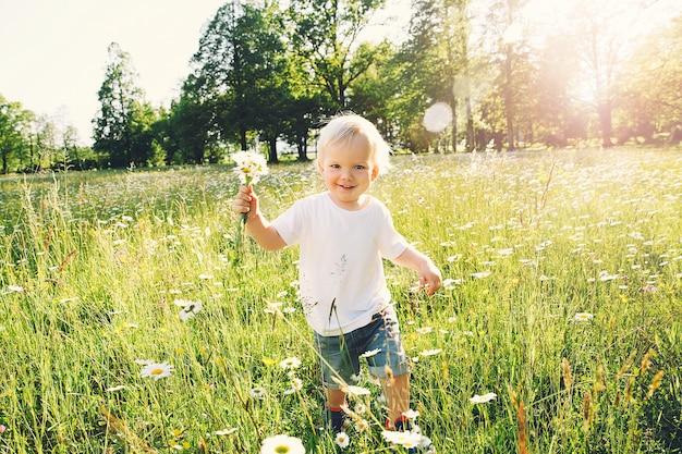 Menino feliz correndo em um prado de flores com um buquê de margaridas silvestres