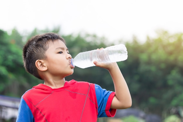 Menino feliz criança asiática bebendo água por uma garrafa de plástico. depois de terminar o exercício.