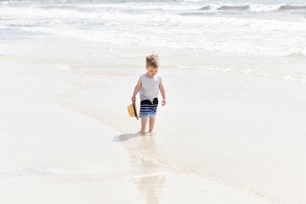 Menino feliz criança de três anos correndo na areia branca