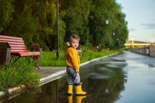 Menino feliz da criança com as botas de borracha na poça em uma caminhada da mola.