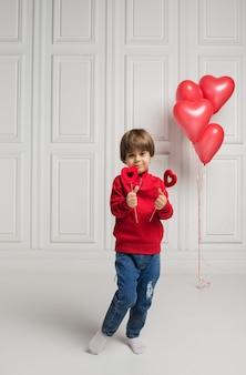 Menino feliz de pé e segurando corações vermelhos em uma vara em um fundo branco