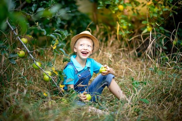 Menino feliz de seis anos com roupas azuis e chapéu sentado na grama em um jardim