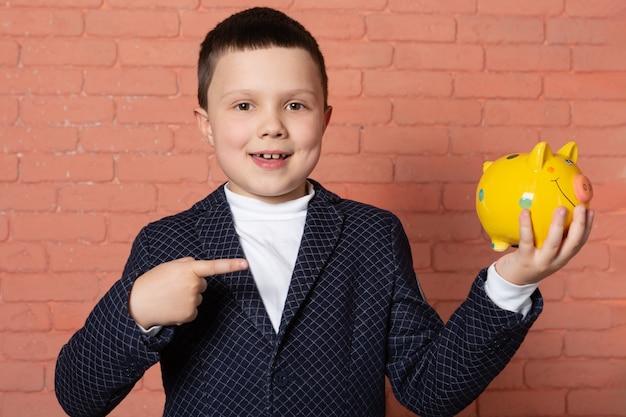 Menino feliz de terno segurando um cofrinho amarelo sobre fundo de tijolo