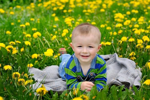 Menino feliz, deitado no cobertor em um prado na primavera