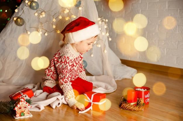 Menino feliz desembrulhando seus presentes de natal em casa criança feliz