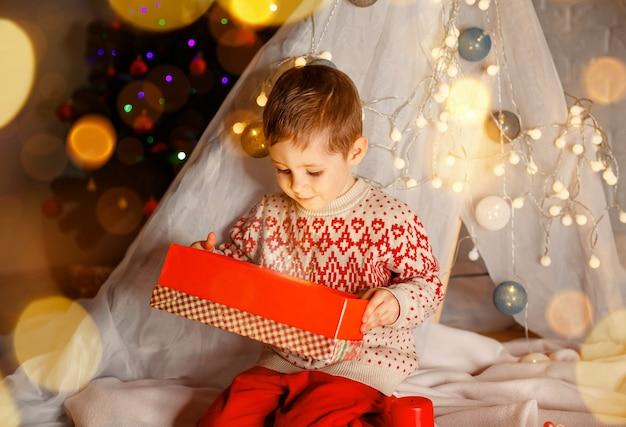 Menino feliz desembrulhando seus presentes de natal em casa e surpreendendo a criança fofa