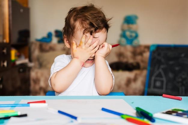 Menino feliz desenha com marcadores coloridos em um pedaço de papel