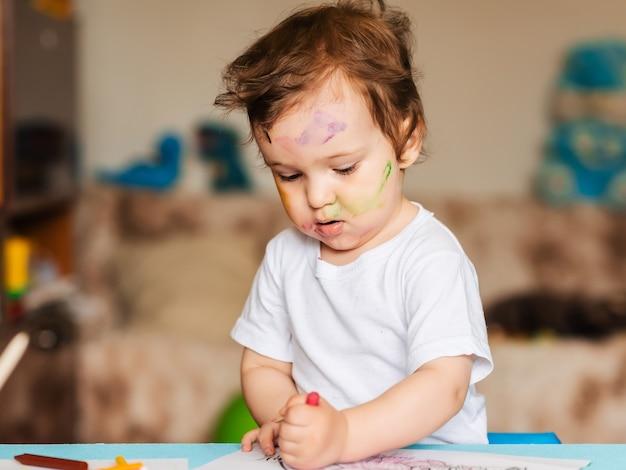 Menino feliz desenhando com lápis de cor em um livro para colorir
