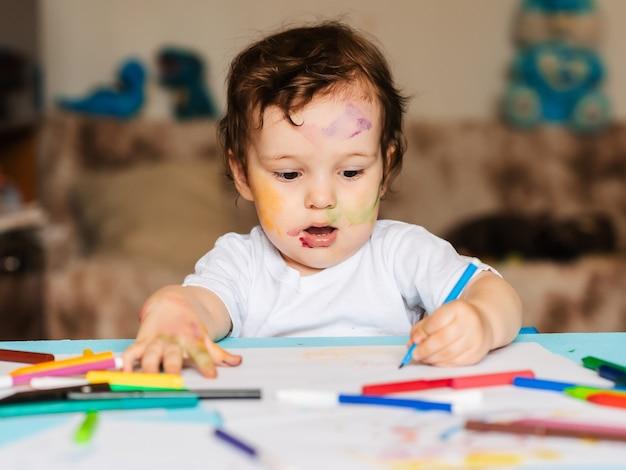 Menino feliz desenhando com marcadores coloridos em um pedaço de papel