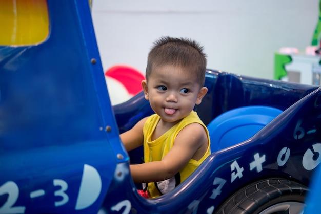 Menino feliz dirigindo um carro de brinquedo