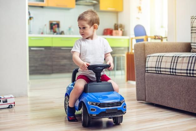 Menino feliz dirigir um carro de brinquedo no apartamento. atividade para uma criança quando fica em casa