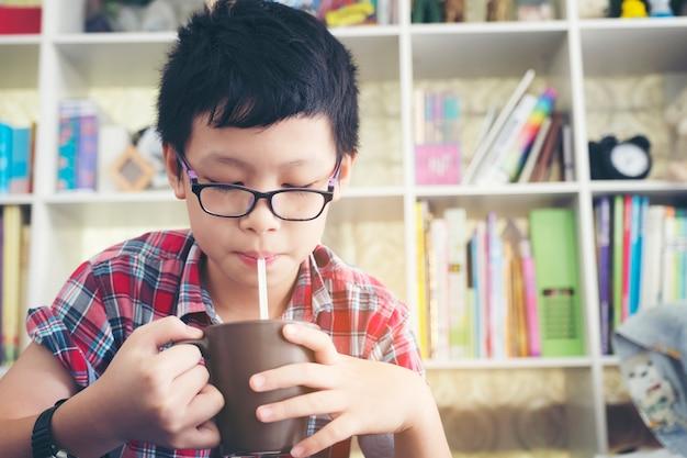 Menino feliz do adolescente que bebe o milk shake que cocktail da palha que senta-se na casa