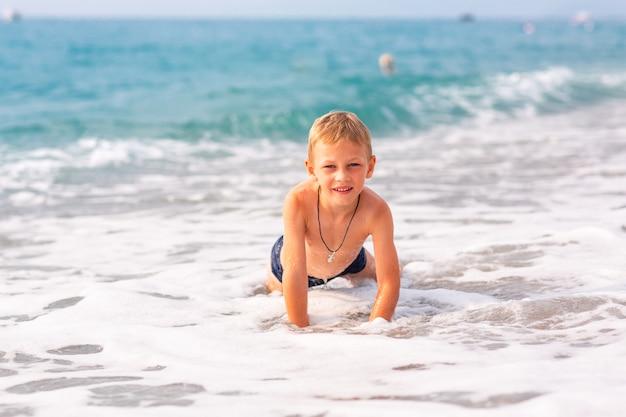 Menino feliz e ativo se divertindo nas ondas à beira-mar