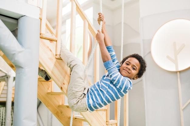 Menino feliz e bonito de etnia africana segurando por uma corda enquanto pendura em uma escada de madeira durante uma brincadeira