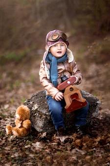 Menino feliz e elegante com a câmera nas mãos em um casaco de couro marrom com um hidromel de brinquedo