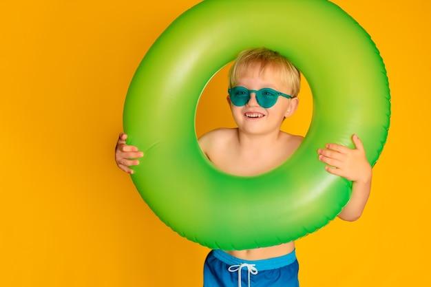 Menino feliz e fofo de 6 a 7 anos de idade em óculos escuros e com uma bóia salva-vidas. o verão e o mar.