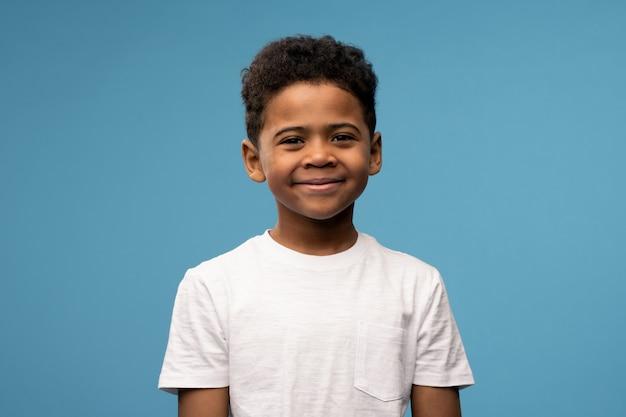 Menino feliz e fofo de etnia africana em uma camiseta branca em frente à câmera contra o azul