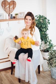 Menino feliz e fofo sentado com a linda mãe em um estúdio decorado com estilo, olhando para a frente