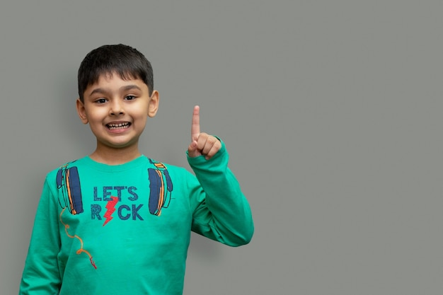 Menino feliz e sorridente apontando o dedo para o espaço da cópia isolado sobre o fundo liso