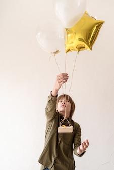 Menino feliz e sorridente brincando com balões de hélio