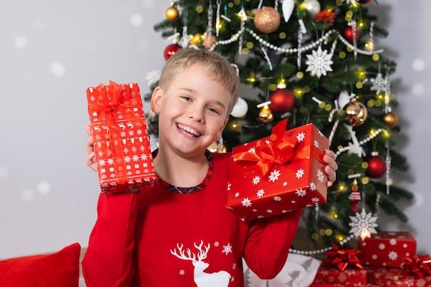 Menino feliz e sorridente com caixas de presente de natal perto da árvore de natal