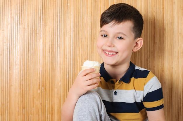 Menino feliz e sorridente comendo sorvete em uma xícara de waffle perto da parede de bambu