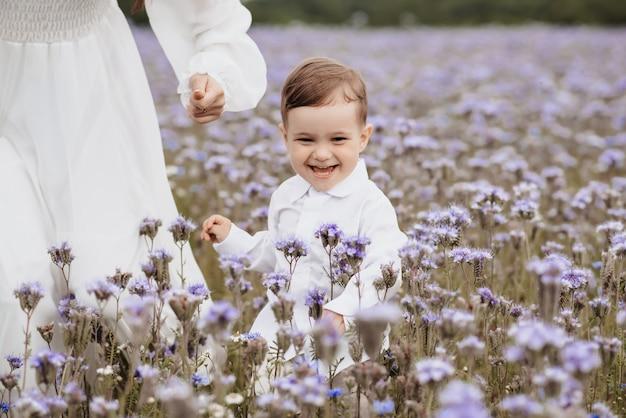 Menino feliz e sorridente correndo por um campo florido
