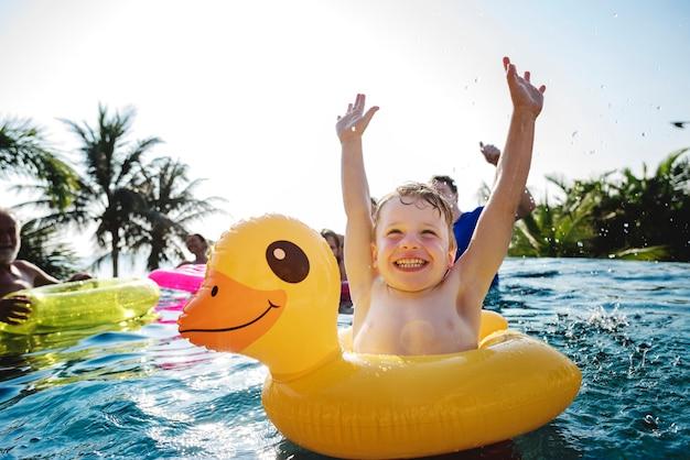 Menino feliz e um tubo de pato amarelo na piscina