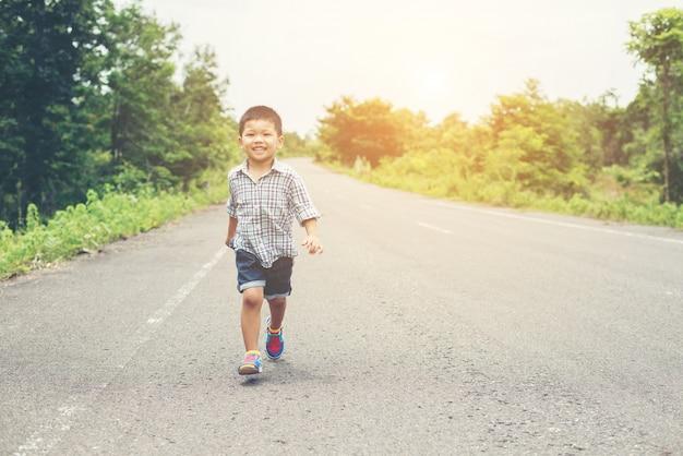 Menino feliz em movimento, smiley correndo na rua.