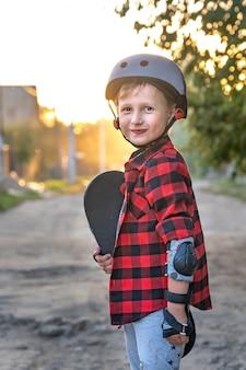 Menino feliz em pé na estrada, segurando um skate com as mãos