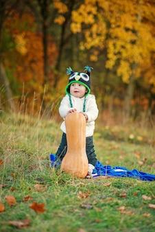 Menino feliz em um boné de malha e roupas quentes, ficar com abóbora no gramado entre as árvores de outono.
