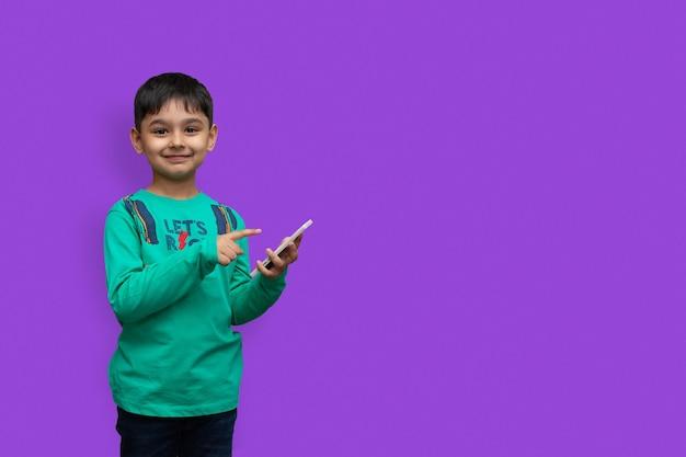 Menino feliz em uma camisa apontando para cima e segurando o braço branco olhando para a câmera sobre fundo isolado e espaço de cópia