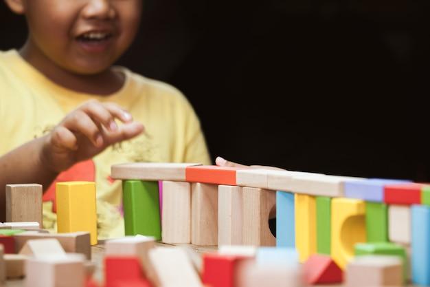 Menino feliz está brincando com blocos de madeira coloridos no tom de cor vintage