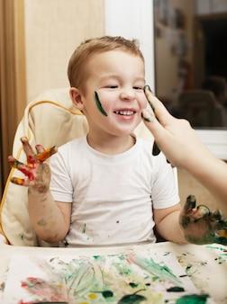 Menino feliz fazendo pintura a dedo