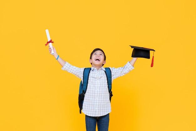 Menino feliz graduação com tampa acadêmica, sorrindo e levantando as mãos comemorando o dia da formatura isolado na parede amarela