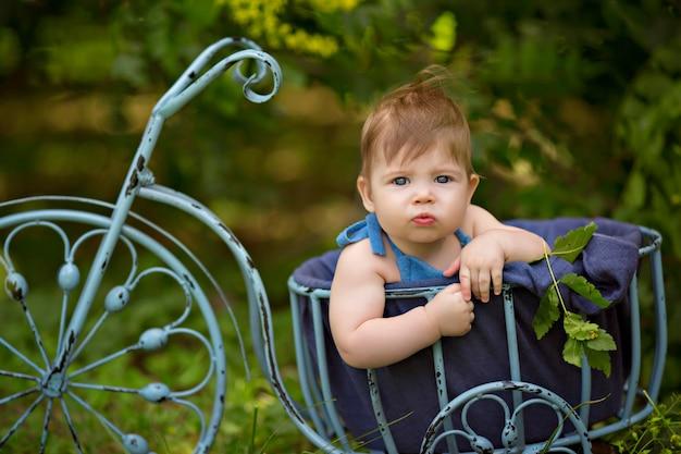 Menino feliz infantil 8-12 meses de idade sentado em uma bicicleta de brinquedo na natureza.
