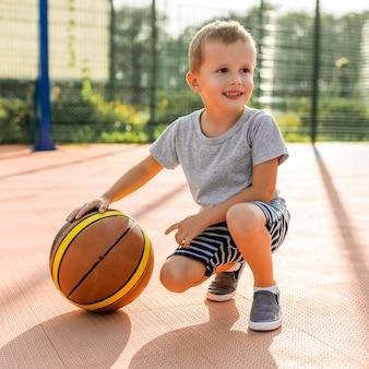 Menino feliz jogando basquete ao ar livre