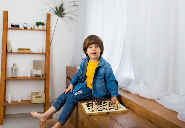Menino feliz jogando xadrez na sala