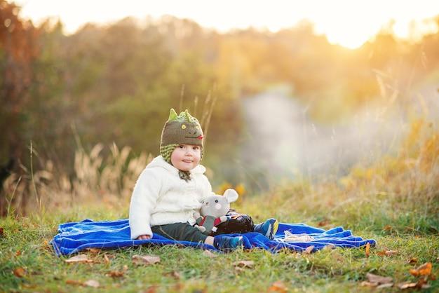Menino feliz mostra uma língua, sentado em uma manta azul e brincando com brinquedos em um gramado verde ao pôr do sol.