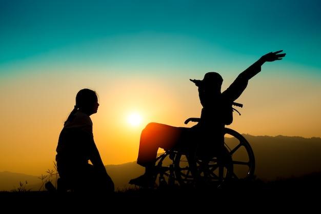 Menino feliz na cadeira de rodas e irmã no por do sol. conceito de criança deficiente feliz
