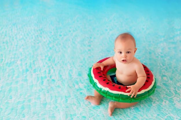 Menino feliz nadando no mar em uma bóia salva-vidas em forma de melancia