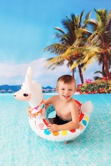 Menino feliz nadando no mar em uma bóia salva-vidas